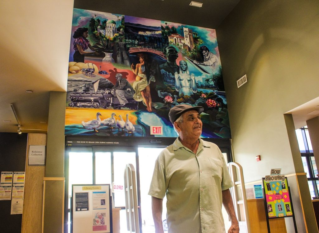 Ernesto De La Rosa stands in front of the mural he painted at the Los Angeles Public Library